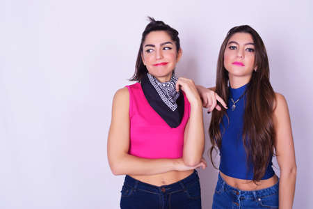 pijamada: Portrait of two beautiful caucasian women. Friendship concept. Trendy and stylish friends isolated over grey background.