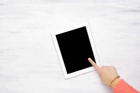articulos de oficina: Mujer que se�ala algo en un gadget tableta, sobre una mesa de madera con elementos de oficina. Vista desde arriba con copyspace.