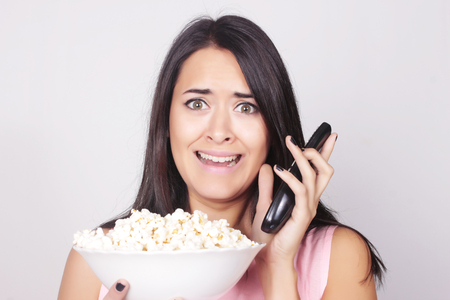 watching horror: Young caucasian woman watching a movie  TV, while enjoying a snack. Girl eating popcorn with scared expression.