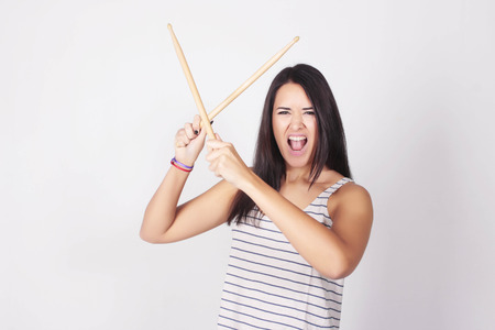 Stylish caucasian young woman holding drum sticks, isolated over grey background. Urban and rock concept. Girl power. Stock Photo