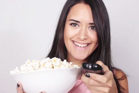 watching horror: Young caucasian woman watching a movie  TV, while enjoying a snack. Girl eating popcorn and pointing the remote control to the camera. Foto de archivo