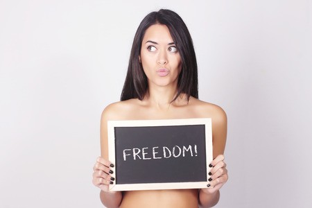 freedom concept: Carefree woman holding a chalkboard saying Freedom. Happiness and freedom concept.