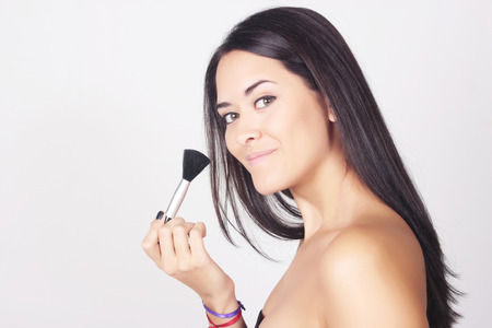 beautify: Closeup of young beautiful woman applying foundation powder or blush with makeup brush. Beauty makeup caucasian woman isolated over grey background. Stock Photo