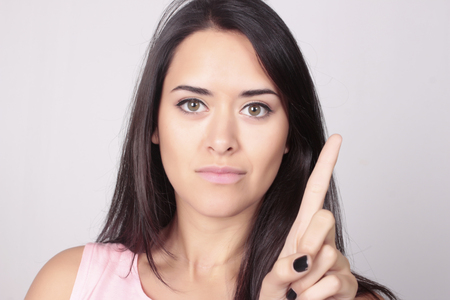 Young beatiful caucasian woman counting one over white background. Hand counting, one finger.
