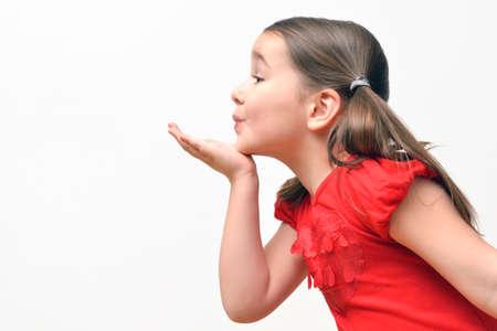 bacio: Dolce bambina che soffia baci, indossando una t-shirt rossa con cuori