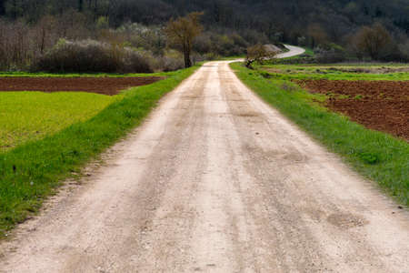rough road: Rough gravel road in the countryside leading far into distance, ending with a curve