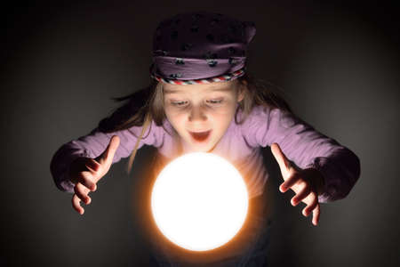 soothsayer: Cute little gypsy girl showing amazement over a glowing crystal ball, predicting the future