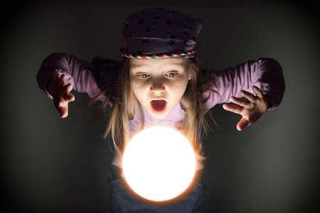 adivino: Peque�a muchacha linda gitana sorprendido m�s de una bola de cristal brillante, ver el futuro Foto de archivo