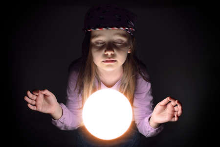 Cute little girl concetrating over a glowing crystal ball, predicting the future