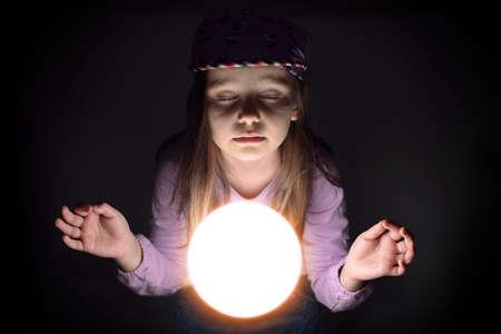 adivino: Ni�a linda concetrating sobre una bola de cristal brillante, predecir el futuro Foto de archivo