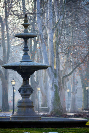 hues: Fountain in the park Zrinjevac, Zagreb, early morning with subtle blue hues and historic lanterns.