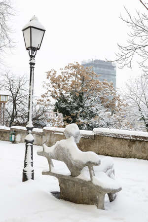 overseeing: A winter view of the famous statue of the croatian writer Antun Gustav Matos overseeing the skyscraper on the main square. Stock Photo