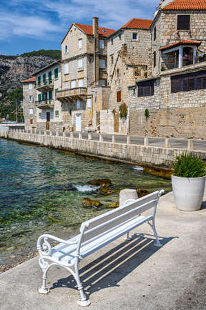 A bench to enjoy the beautiful seaside view of Komiža town on Vis island, Croatia. Stock fotó