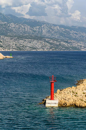 Typical mediterranean red lighthouse on a deserted rocky cape, surrounded by deep blue sea with the storm brewing in the far-away mountains. Stockfoto - 132017712