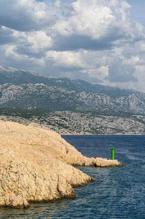 Typical mediterranean red lighthouse on a deserted rocky cape, surrounded by deep blue sea with the storm brewing in the far-away mountains.