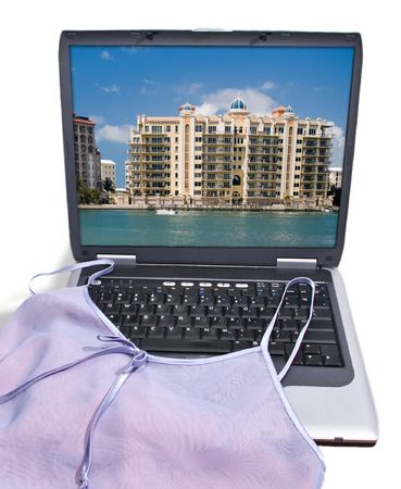 booked: Negligee draped over laptop computer displaying a luxury resort, as if a lady was packing for a  get away she had just booked online.  Isolated on white with clipping path.
