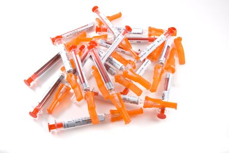 A stack of expended syringes awaiting disposal, on white background  Imagens