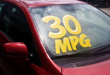 mpg: Car dealer displaying hight miles per gallon on new cars. Stock Photo