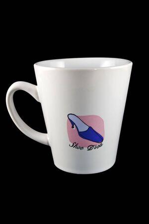 White coffee mug with ladys shoe on it, isolated on black background