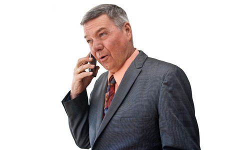 graying: Portrait of a senior businessman, 34 view, talking on a cell phone, isolated on a white background. Stock Photo