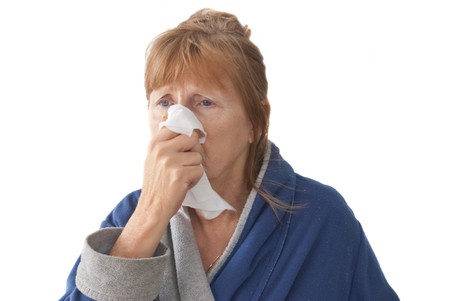 Mature woman with cold wearing housecoat and blowing nose, isolated on white backbround Stock Photo - 4329126