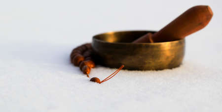 Tibetan singing bowl lying on the snow along with the rosary. Blurry.