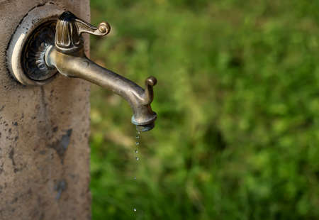 A drop of water close up. Old copper tap.