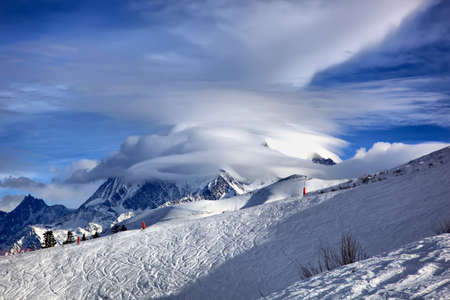 Beautiful clouds over the peak of Mon Blanc on a sunny winter day. Haute Savoy, French Alps.