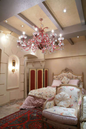 splendid bedroom in classical style with easy chair on luxurious rug under beautiful chandelier