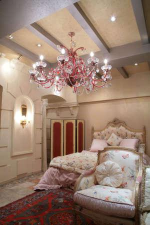 splendida camera da letto in stile classico con poltroncina di lusso a tappeto sotto bella lampadario