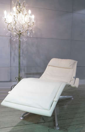 candelabrum and white leather easy chair with armrest for relaxation photo