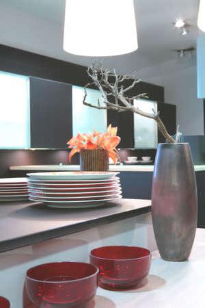 frammento del tavolo da cucina con piatti, ramo e fiori in vaso