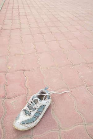 outbound: old thrown away sneakers on sidewalk
