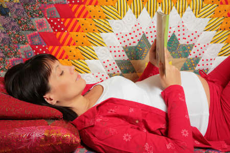 expectant mother with dark hair is reading book photo