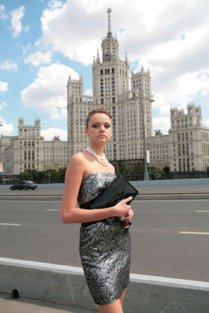 serious beautiful girl in black-silvery dress on background of the old moscow skyscraper photo