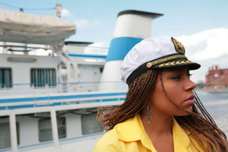 close-up portrait of the girl in yellow cloth and in captain cap on background of the sailboat Stock Photo - 3496988