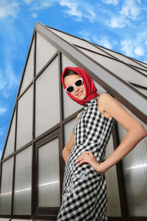 beautiful girl in the plaid dress with red kerchief and stylish sunglasses photo