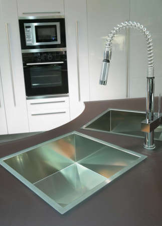trendys metallic sink with graceful faucet on the super-modern kitchen