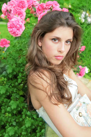 splendid: portrait of the beautiful girl on background of the bush of the roses