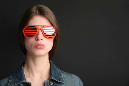 splendid: female portrait in red sunglasses on the black background Stock Photo