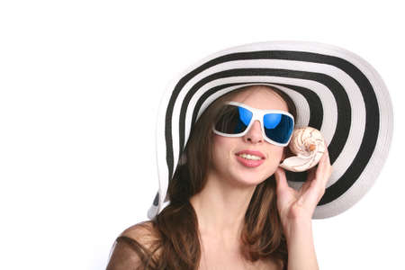 smiling beautiful woman in striped hat and black sunglasses listens seashell photo
