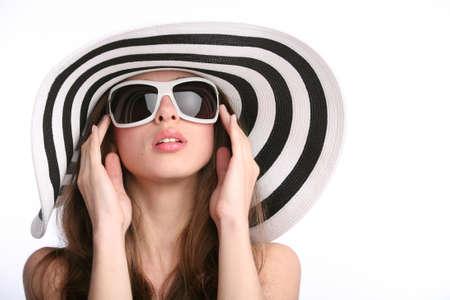 bella ragazza con il cappello a righe e occhiali da sole con le mani vicino a faccia sul fondo bianco