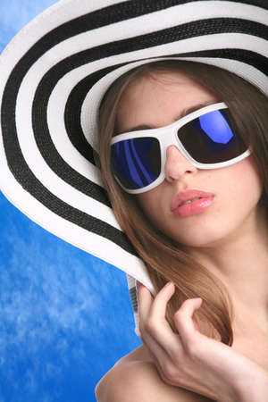 beautiful young woman in striped hat and sunglasses on background of the blue sky