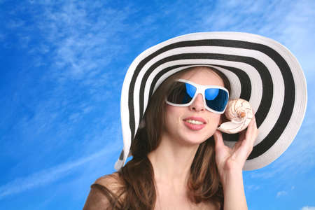 smiling girl in striped hat and black sunglasses listens seashell photo