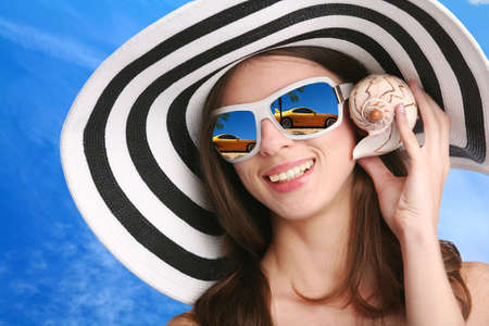 smiling young woman in striped hat and black sunglasses listens seashell