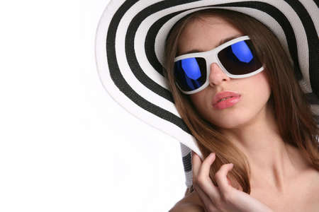 young woman in striped hat and sunglasses on background blue sky photo