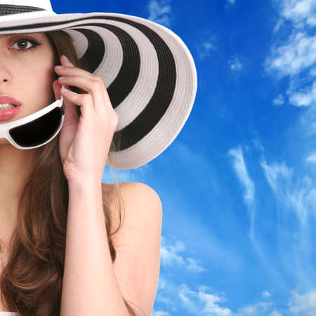 crop portrait of the beautiful girl in striped hat and sunglasses on background blue sky