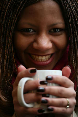 close-up portrait of the beautiful black woman with white mug in hand. small depth to sharpness photo