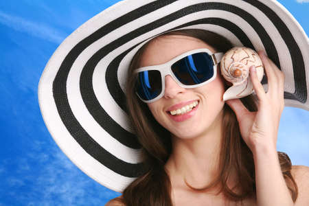 smiling young woman in striped hat and black sunglasses listens seashell photo