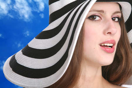 beautiful girl in striped hat on background blue sky photo